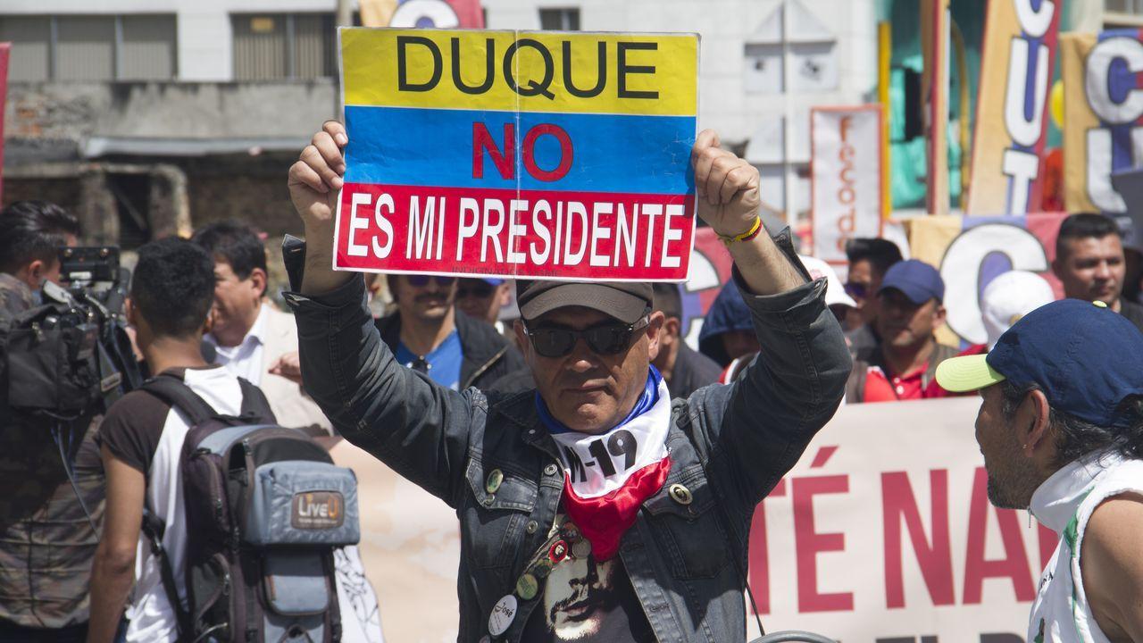 Un manifestante muestra un cartel contra el presidente Duque en una calle de Bogotá