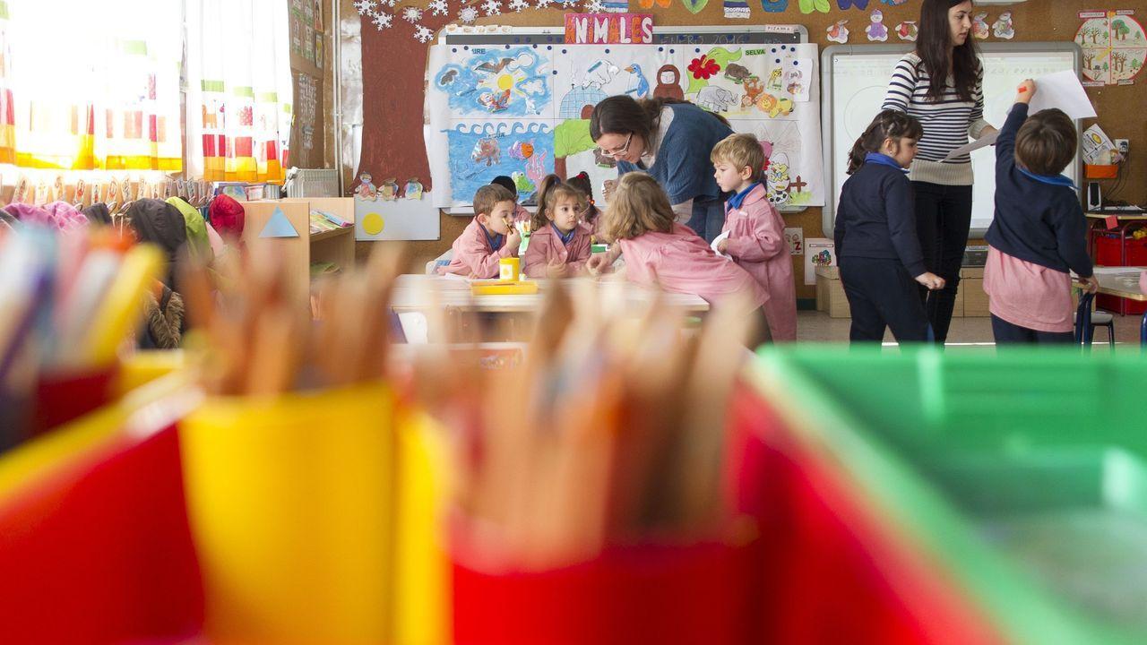 cole.Un profesor pone una mascarilla a un niño de Infantil en el CEIP Raquel Camacho de A Coruña