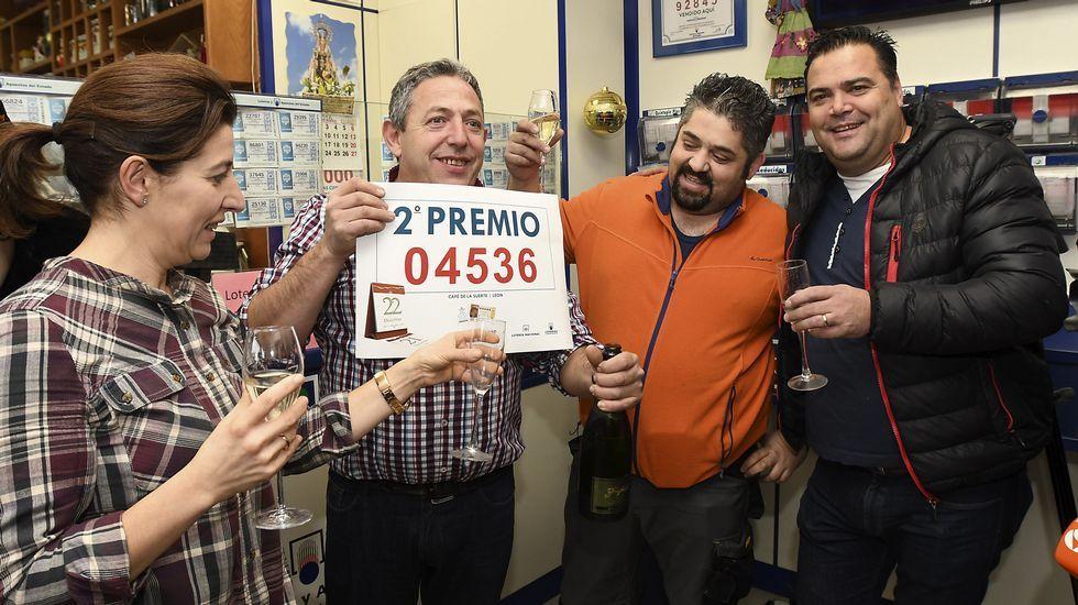 Manuel Martínez, propietario del Café de la Suerte de León, y el agraciado Roberto Raposo, celebran en el interior del establecimiento el segundo premio