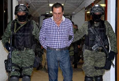 El capo Héctor Beltrán Leyva es trasladado por dos militares tras su captura en un refugio de artistas.