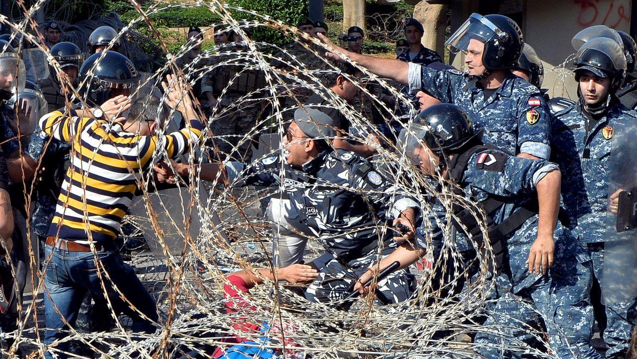 Varios manifestantes se enfrentan a los agentes de policía mientras tratan de traspasar la concertina que los separa para dirigirse hacia el Parlamento