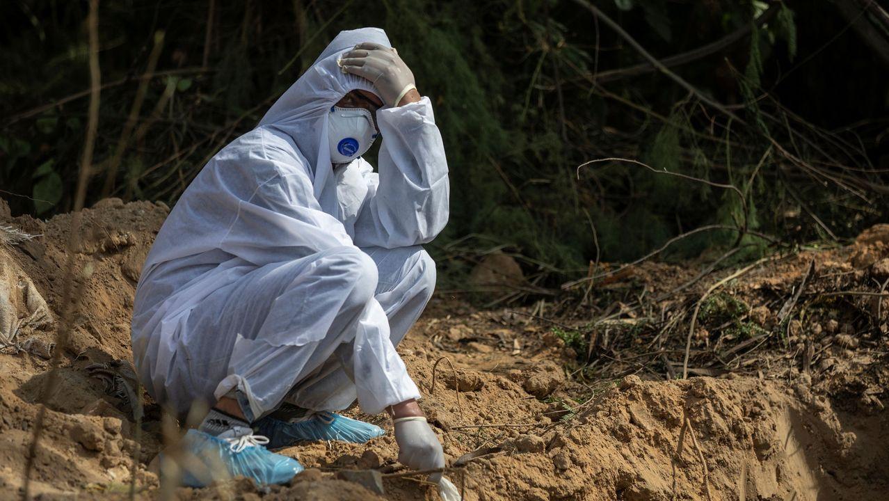 Un familiar se despide de una víctima del coronavirus ante una fosa común en Nueva Delhi, La India