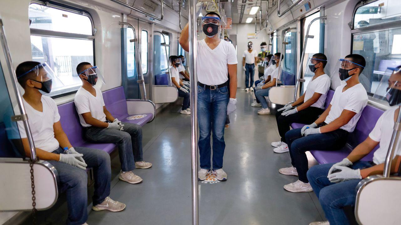 Alumnos de la academia de policía de Filipinas simulan la distancia social adecuada en el transporte público durante un ejercicio