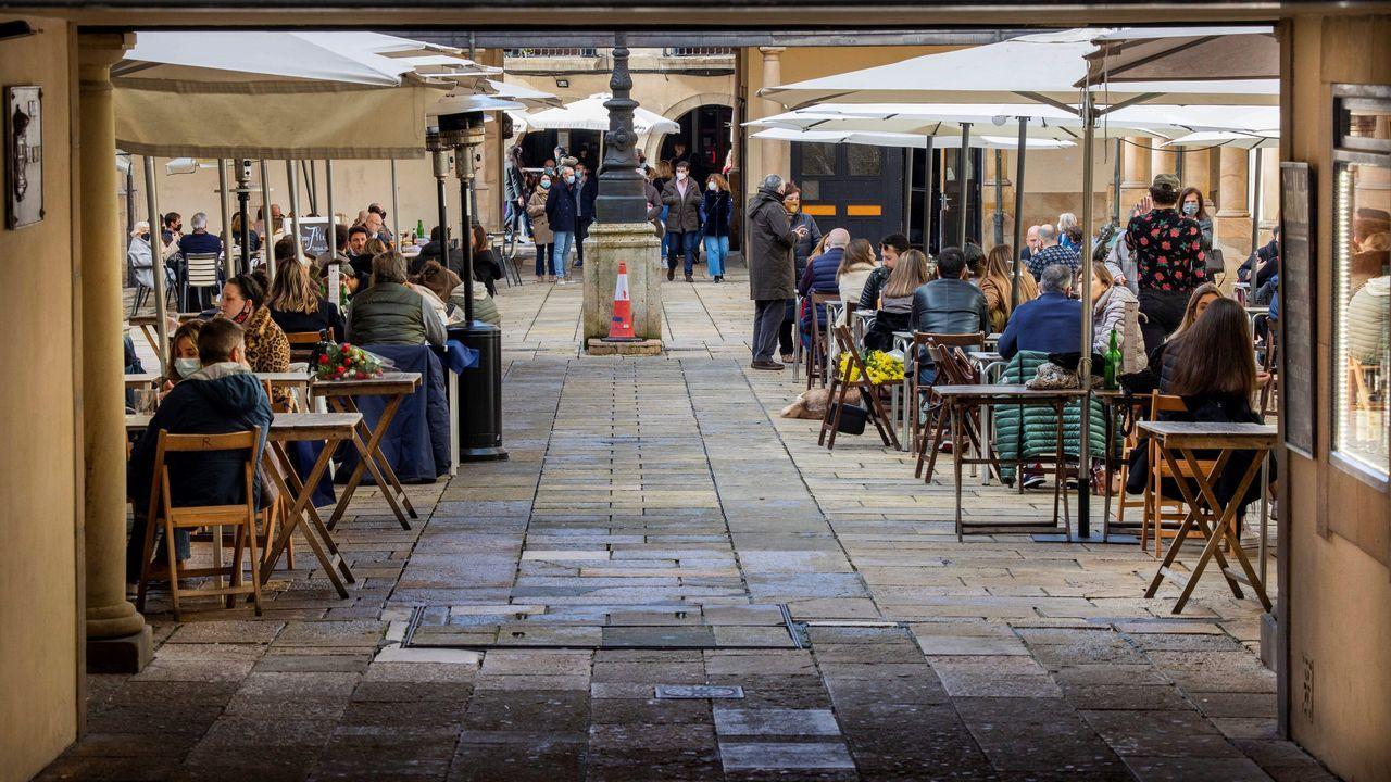 Paseantes en Oviedo. Varias personas disfrutan en una terraza de un bar de la ciudad