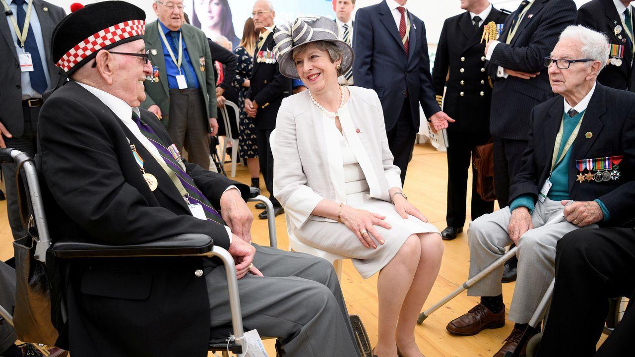 May charla con veteranos en  durante una ceremonia en el cementerio de la Commonwealth con motivo del 75º aniversario del desembarco de Normandía