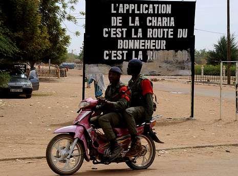 Soldados pasan cerca de un cartel islamista en Gao.