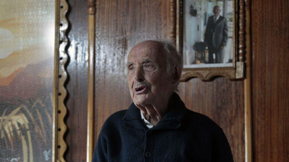 Ruperto Álvarez no salón da súa casa, con marcos e molduras de madeira feitas por el
