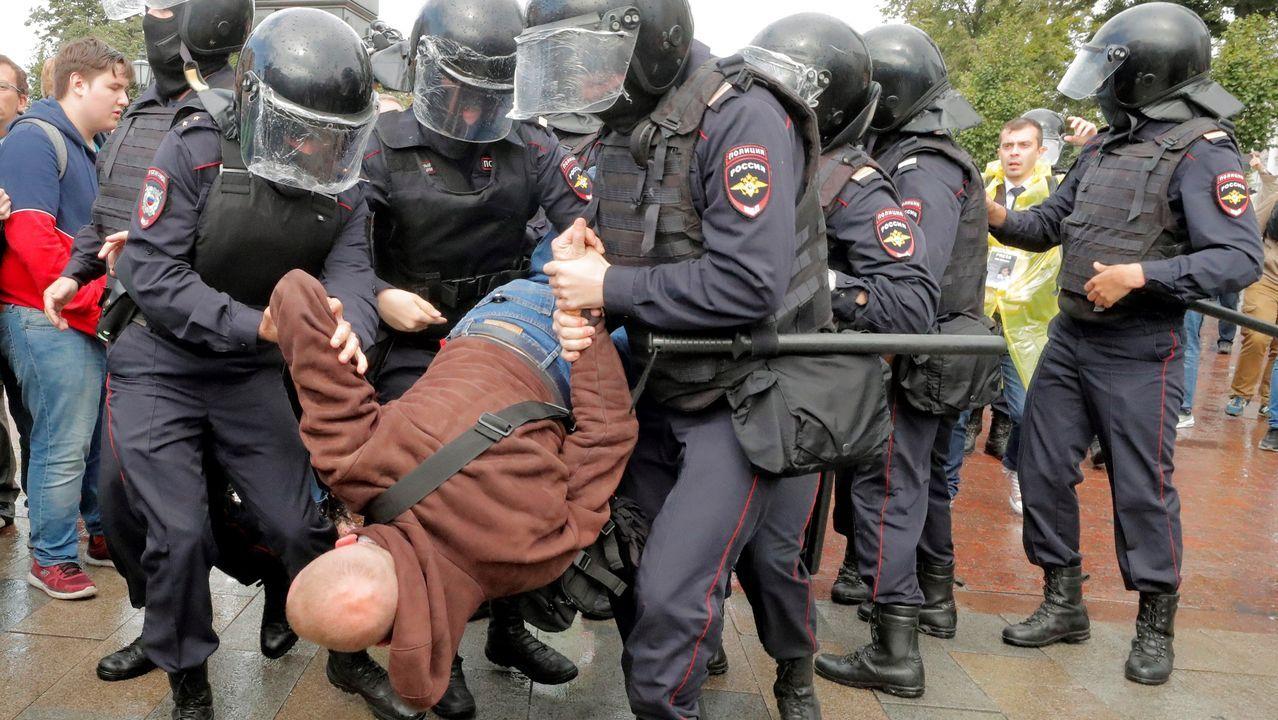 Los antidisturbios llevan en volandas a un manifestante que participaba en la protesta no autorizada contra Putin
