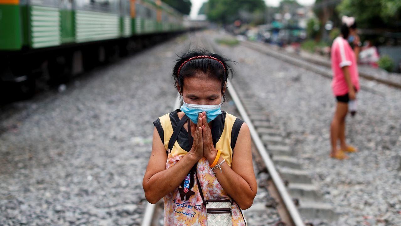 Una mujer con mascarilla aguarda el tren en un barrio deprimido de Tailandia
