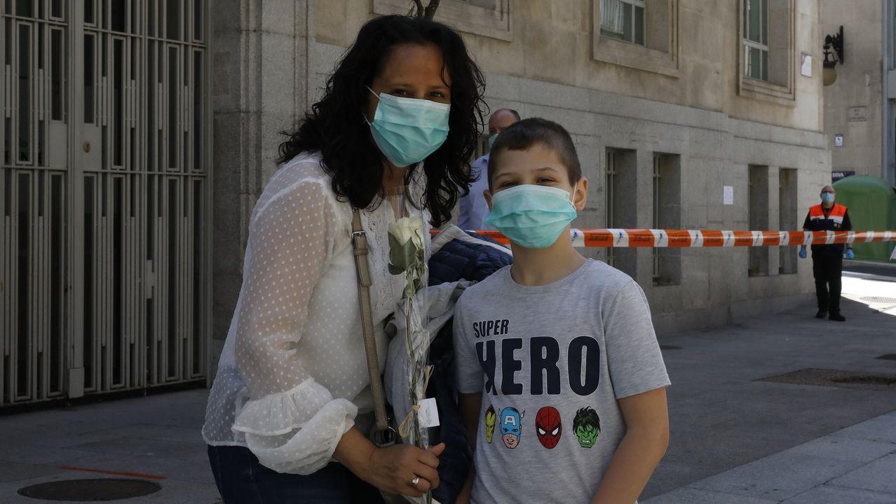 DÍA DE LA MADRE.Hijo y madre ante el puesto municipal con rosas blancas
