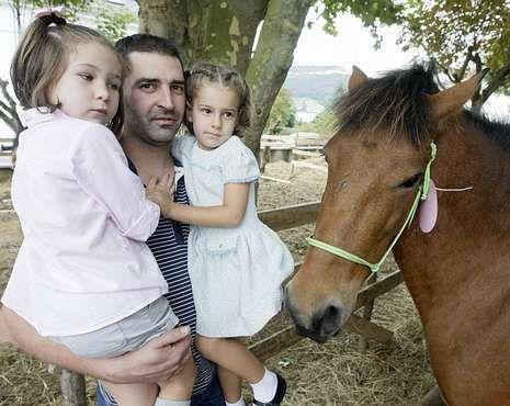 Un papá, descubriendo a sus hijas los caballos de As San Lucas.