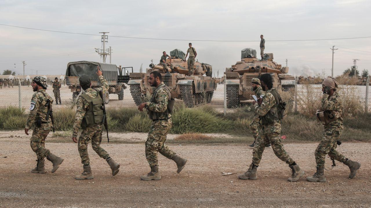 Milicianos sirios a los que apoya Ankara pasan por un campamento de tropas turcas