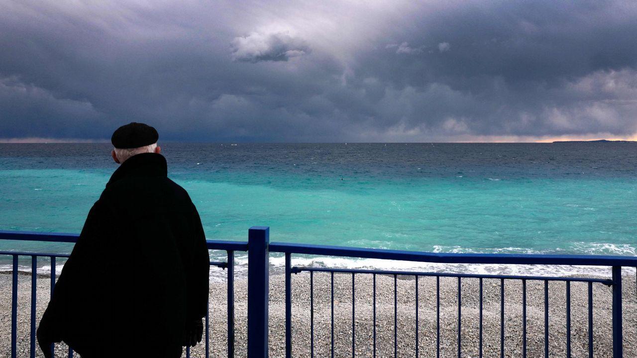 Un hombre camina mirando el mar Mediterráneo en la ciudad de la Riviera francesa de Niza, en el sureste de Francia