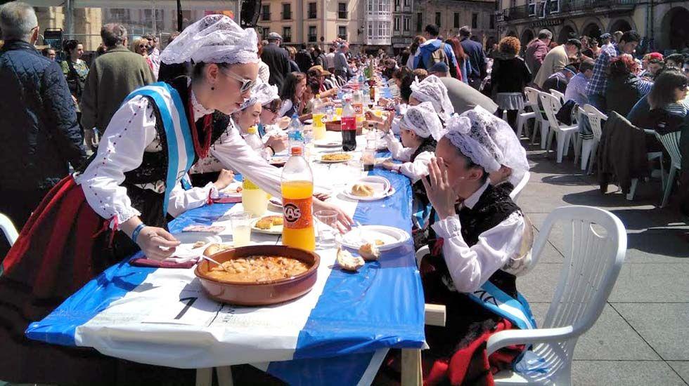Jovenes vestidas de asturiana comparten la comida en la calle de Avilés.Las xanas y xaninas de las fiestas de El Bollo