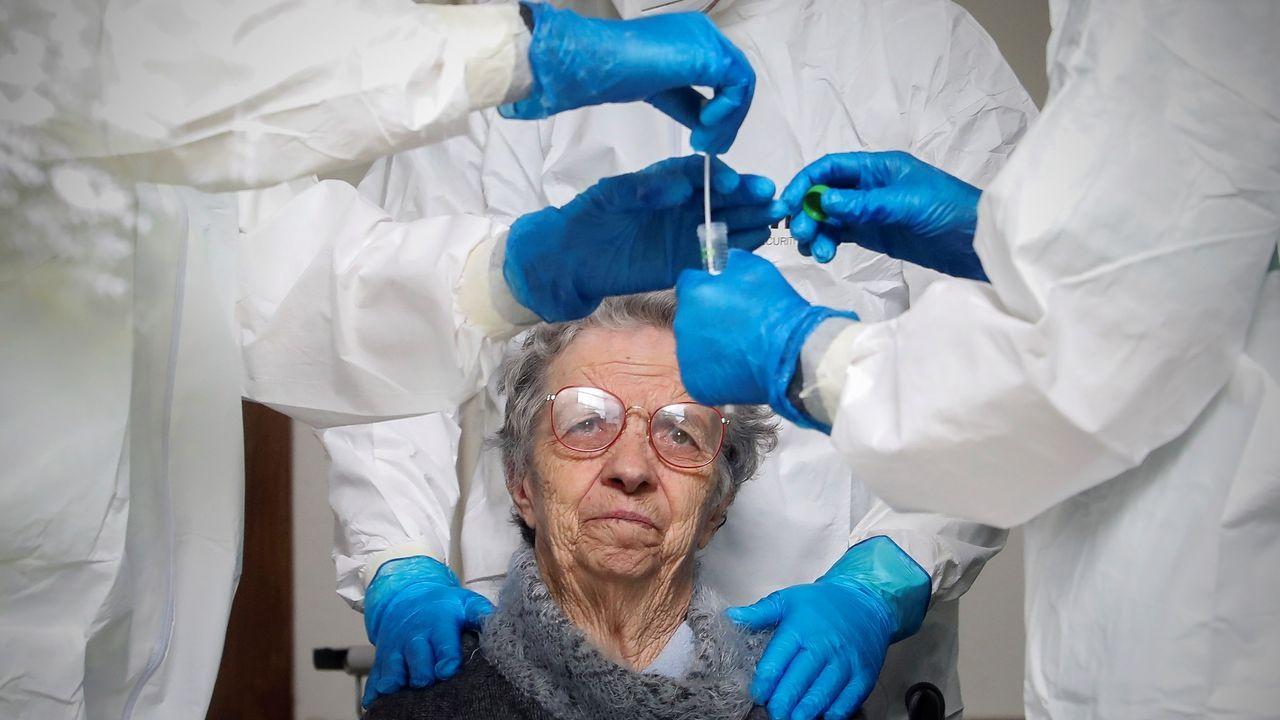Un mujer observa al personal sanitario tras hacerse una prueba de coronavirus