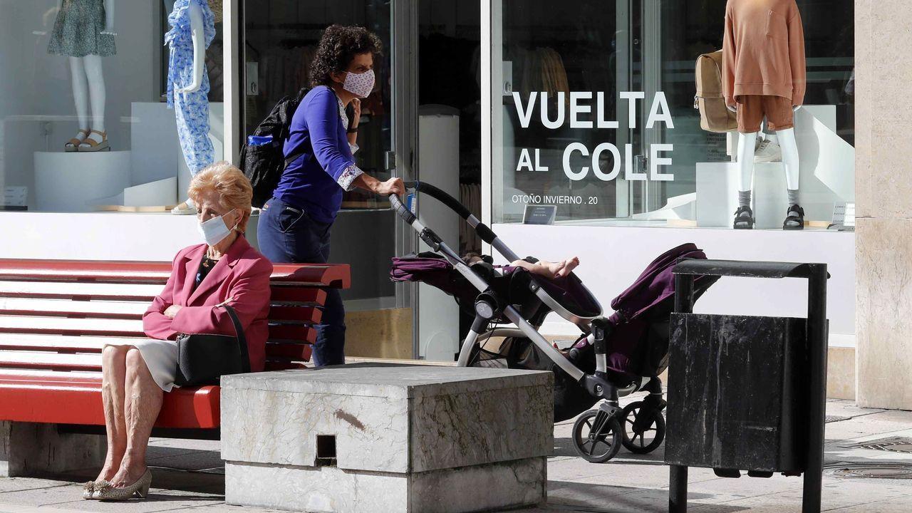 Una mujer camina frente a un escaparate con la campaña de la vuelta al colegio en una calle del centro de Oviedo