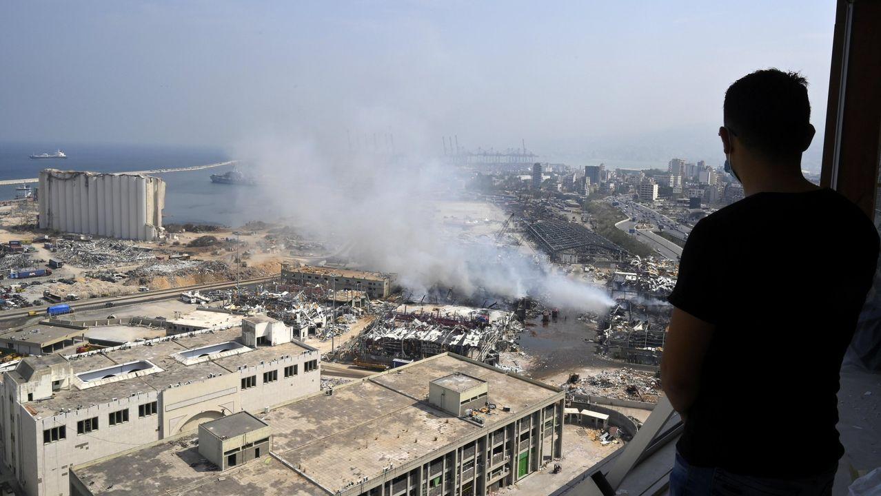molina.Un libanés observan la extinción del incendio otro gran incendio en el almacén donde la Cruz Roja Internacional guardaba cerca del puerto la ayuda humanitaria volvió a despertar los fantasmas del desastre.