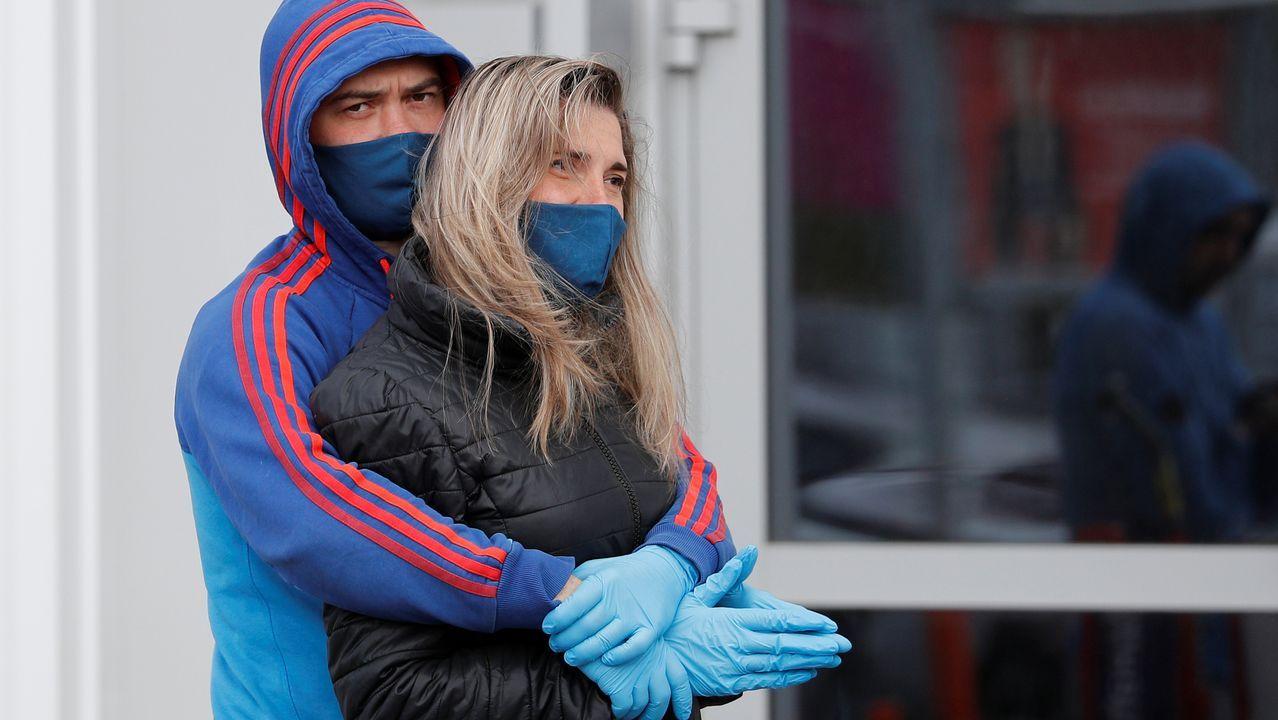 Una pareja se abraza en Kaliningrado, en Rusia, mientras espera delante de uno de los comercios que ya reabrieron