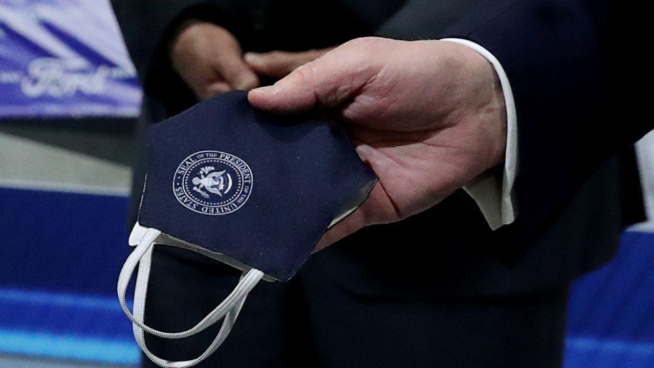 Trump sostiene una mascarilla con el distintivo de la Casa Blanca