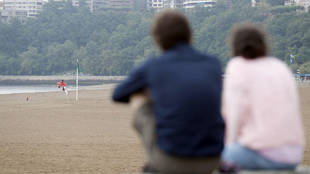 Una pareja observa la playa vizcaína de Erega, sin bañistas como consecuencia del mal tiempo en la cornisa cantábrica