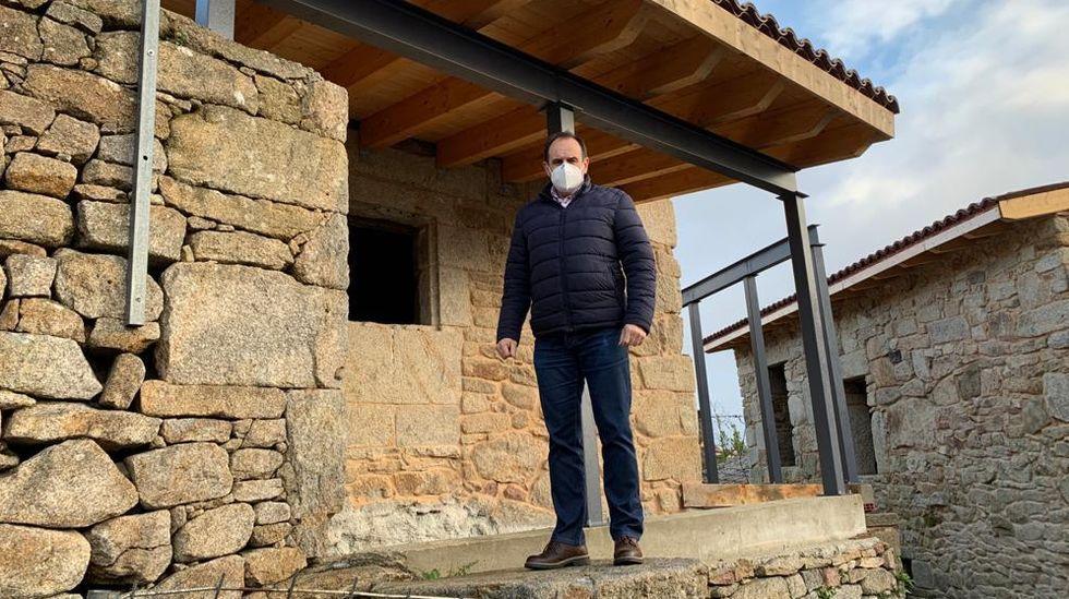 El alcalde de Parada, Aquilino Domínguez, junto a una de las casas que están rehabilitando en Fondodevila