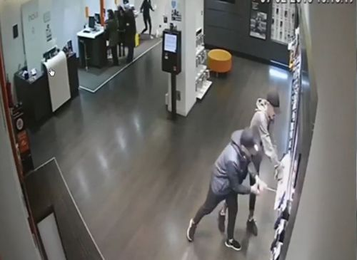 Dos ladrones grabados por una cámara de seguridad mientras arrancan los móviles en una tienda de telefonía