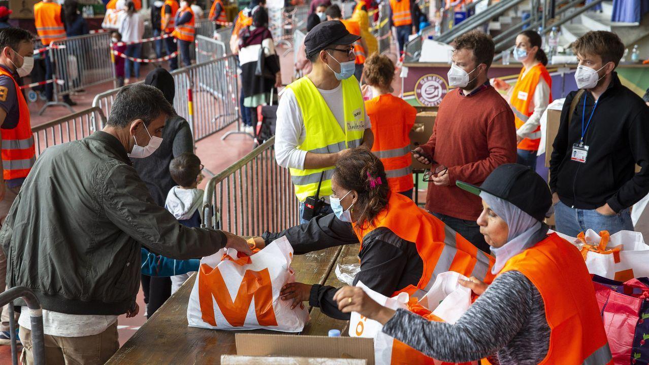 Voluntarios distribuyen alimentos a los más necesitados en Ginebra, Suíza, cumpliendo con el distanciamiento y las mascarillas