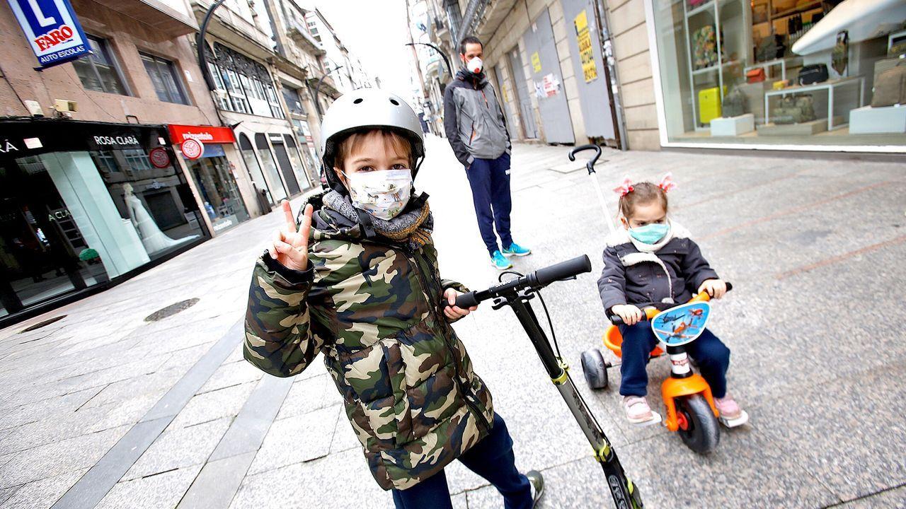 Dos niños con mascarilla por las calles de Vigo