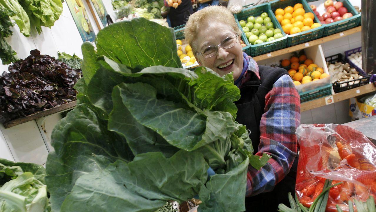 Maribel Fonticoba, con un hermoso repollo de Betanzos, una de las verduras de temporada que triunfa en su puesto