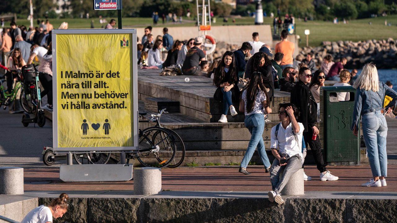 Numerosos jóvenes disfrutan de un día de sol en Malmo, Suecia, donde un cartel pide que mantengan la distancia de seguridad