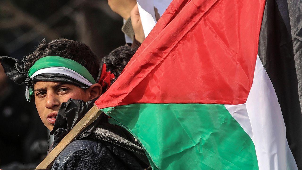 Un niño sostiene una bandera palestina durante una protesta en Gaza contra el plan de Trump