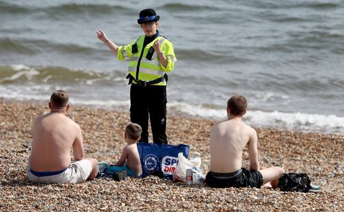Arte, oración y colas para ir a la playa.Una agente británica invita a unos bañistas a abandonar el arenal de Brighton, en el sur de Inglaterra