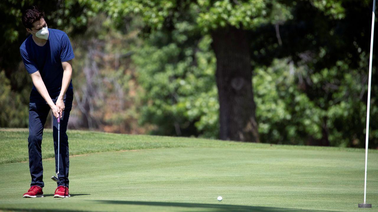 El golfista Alberto Mazatan usa una máscara facial en el campo de golf Eaton Canyon, en Pasadena, Estados Unidos