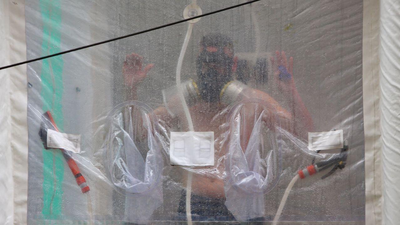 Un soldado usando la ducha especial instalada en la calle