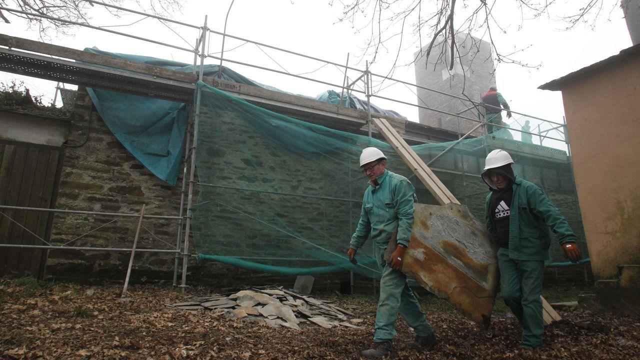 Dos trabajadores retiran una de las losas de pizarra del tejado de la iglesia