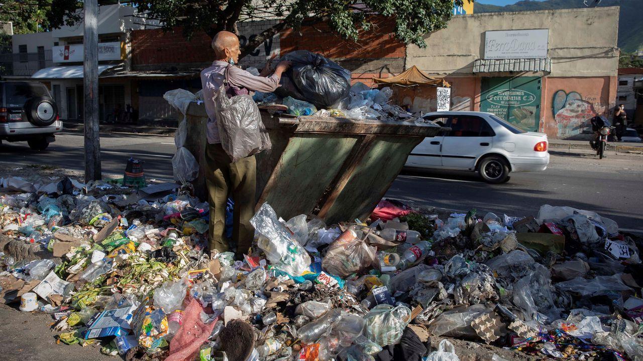 Un hombre busca en la basura en una calle de Caracas