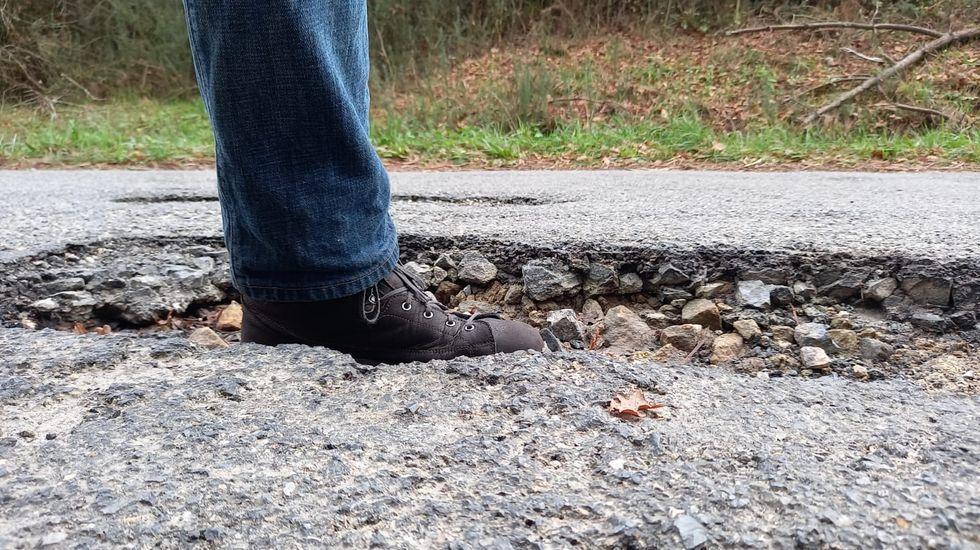 Un vecino introduce un pie en uno de los baches de la carretera de A Barrela a Os Peares para que se vea su profundidad