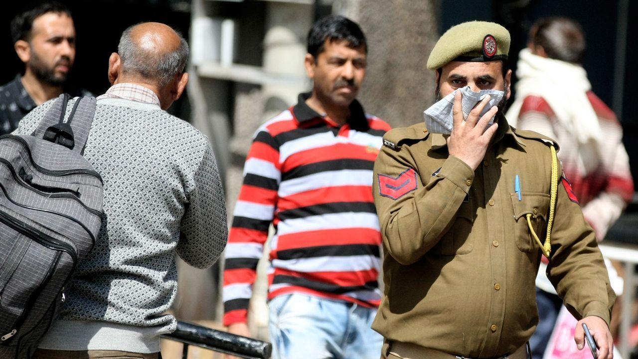 Un policía se cubre la cara en una calle de Jammu, India