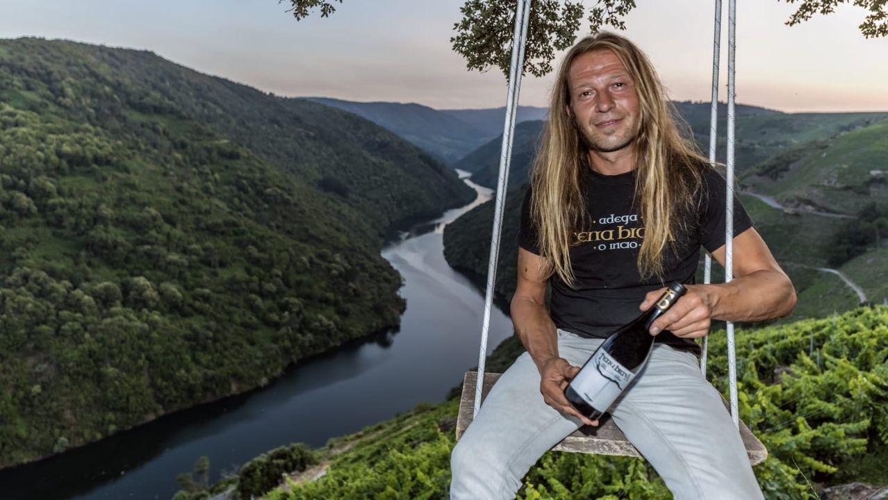 Breogán Pereiro con una de las botellas de la bodega, sentado en el columpio