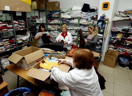 Voluntarios de la entidad vinculada a la Iglesia clasificando ropa en el almacén.