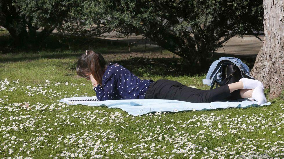 Una joven hoy, tumbada al sol, en el parque de San Francisco de Oviedo