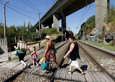 Una familia cruza el paso a nivel situado bajo el puente de Rande el pasado lunes.