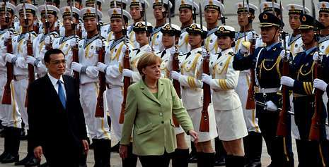 Angela Merkel pasa revista en Pekín a una unidad militar, acompañada por el primer ministro chino Li Keqiang.