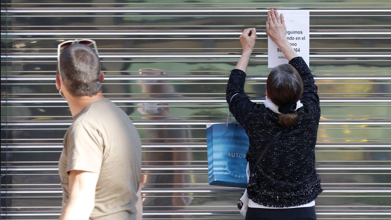 Una mujer coloca un aviso en la persiana cerrada de un negocio del centro de Oviedo