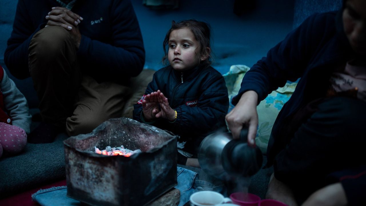 Marjan Hosini, de 3 años, calienta sus manos al lado de sus padres, en un refugio temporal aledaño al campamento de Moria