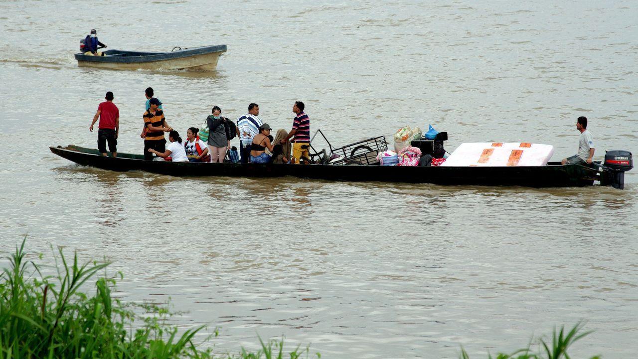 Desplazados venezolanos cruzan en un bote desde La Victoria, en Venezuela, a Arauquita, en en territorio colombiano