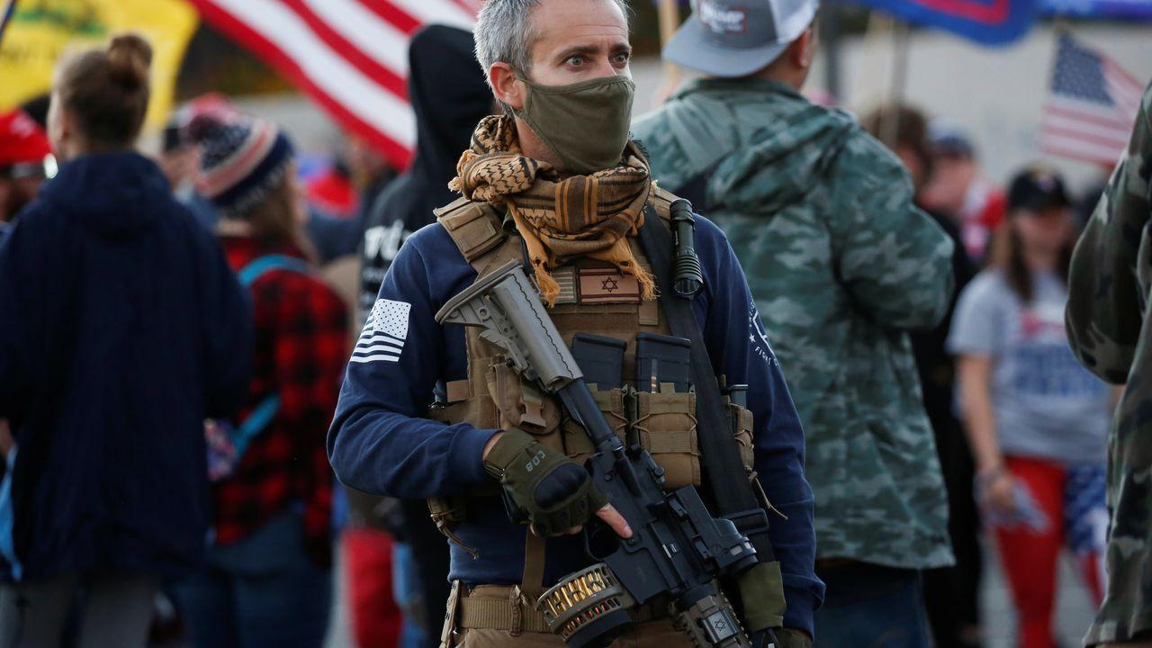 Un manifestante armado con un rifle de asalto protesta contra el recuento frente a un centro de votación de Phoenix (Arizona)