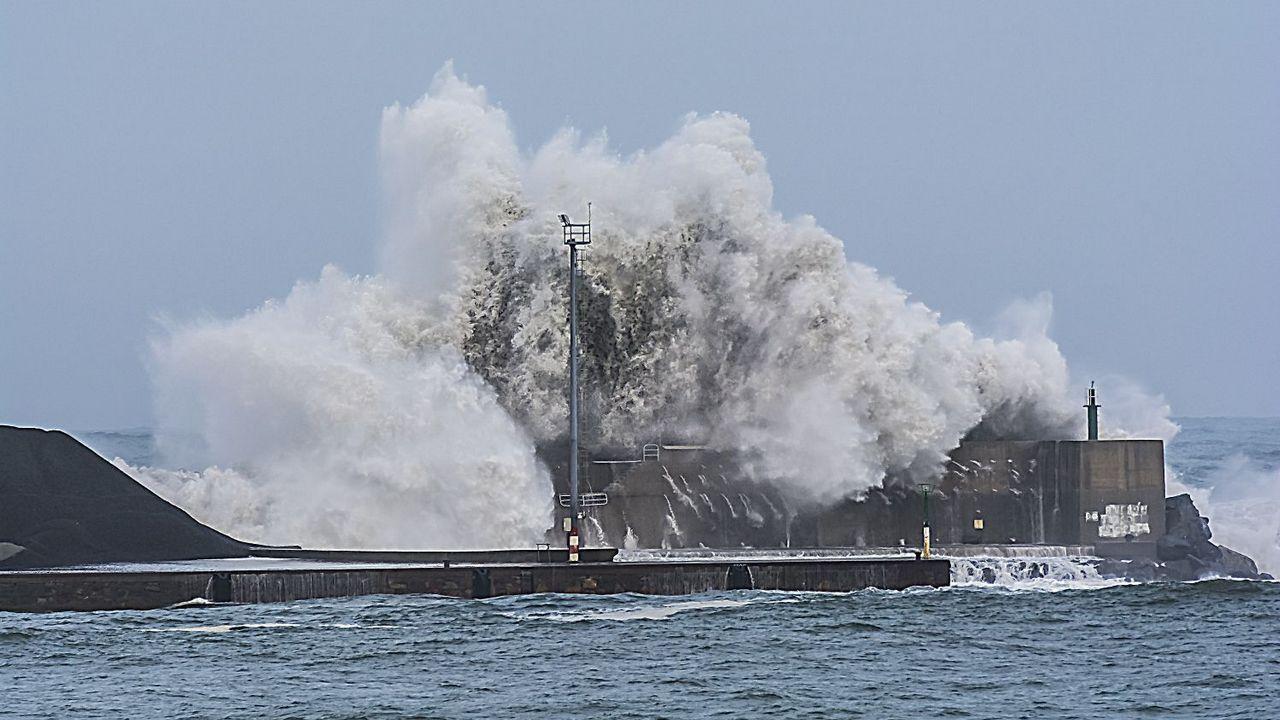 El mar golpea el espigón del puerto de Cariño momentos después de tirar una parte de la escollera