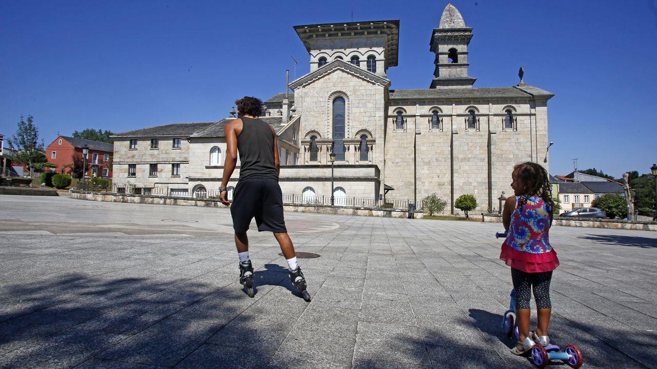 Un joven y una niña en la plaza cercana a la iglesia de Guitiriz