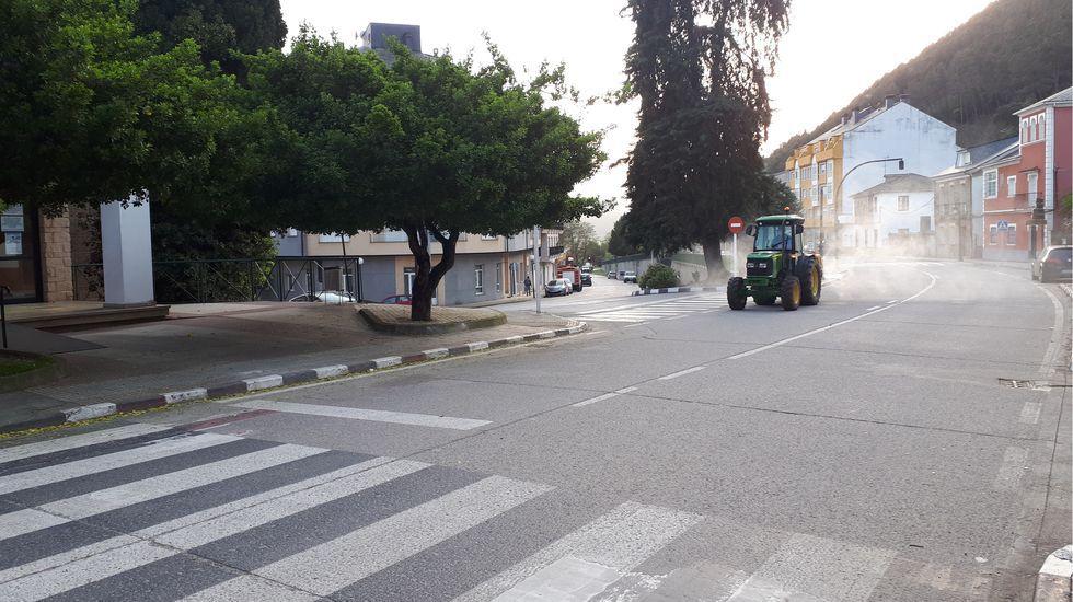Un tractor provisto de un pulverizador desinfecta las calles de Quiroga